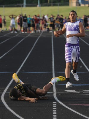 Watkins Memorial senior Desmond Melson lays on the track after falling across the finish line in the 400. He won the event during the Division I regional meet at Pickerington North.
