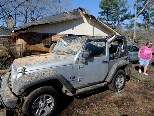 Connie Miller stands next to her jeep that had a tree
