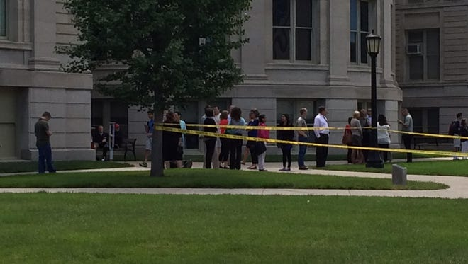 UI students and faculty wait outside Jessup Hall on Monday as the Johnson County Bomb Squad investigates a suspicious backpack left in the building.