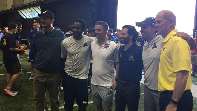 From left, Michigan coach Jim Harbaugh stands with former U-M star Desmond Howard, Buffalo Bills president Russ Brandon, Beaumont's Dr. Justin Trivax, passing game coordinator Jedd Fisch and basketball coach John Beilein on Saturday, June 18, 2016 in Ann Arbor.