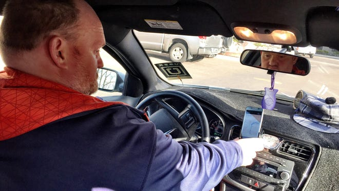 Great Falls resident Mike Otis, who drives part time for Uber, checks his smartphone application for an assignment.