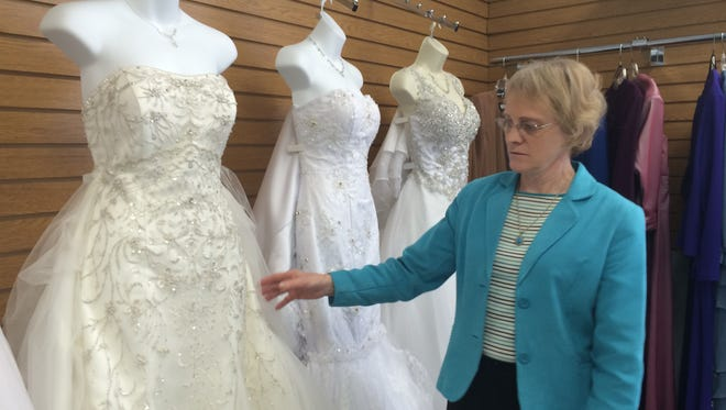 Kathy Pechinski shows off one of the many wedding dresses in her Wisconsin Rapids bridal shop.