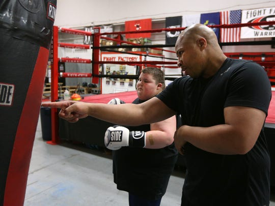 Christopher Rhabb, right, working with  Tyler Rust, 16,  at Rochester Fight Factory.  Rhabb has offered to help Tyler get more  healthy and control his weight better.