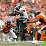 Philadelphia Eagles running back LeSean McCoy, center, leaps between Denver Bronco defenders Rahim Moore, left, and Wesley Woodyard, right, during the third quarter at Sports Authority Field at Mile High in Denver, Colorado, Sunday, September 29, 2013. The Broncos defeated the Eagles, 52-20. (David Maialetti/Philadelphia Daily News/MCT)