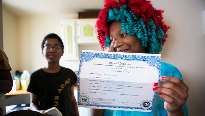 Trinity Neal shows her mother her new birth certificate that just arrived in the mail with the gender change to female.