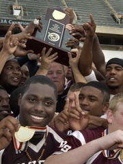 Pensacola High head football coach Mike Bennett, background center, joins his players in 2009 as they hold up their Class 3A state championship trophy (and medallions) they won by beating Belen Jesuit 28-7 in the Florida Citrus Bowl stadium.