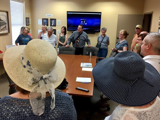 Anja Rowland of Henderson, at left in white hat, and Karla Gaynor of Evansville, at right in blue hat, listen as local historian Frank Nally begins Saturday's W.C. Handy- themed history walk at The Depot welcome center on the Riverfront.