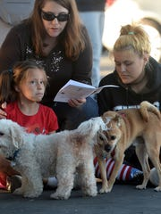 Valerie Ortiz and her daughters (from left) Allie and Amber with their dogs attend The Blessing of Animals hosted by Saint Paul's Episcopal Church in Ventura on Saturday.