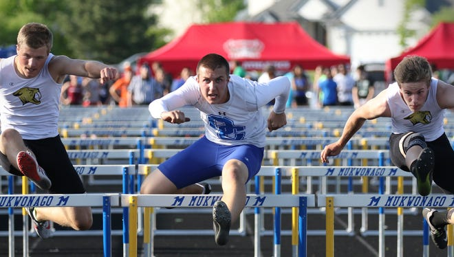 Oak Creek's Dan Cramer battles Franklin's Noah Rugaber (left) and Cole Stugelmeyer in the 110-meter hurdles during the Mukwonago sectional meet at Mukwonago High School on May 24.