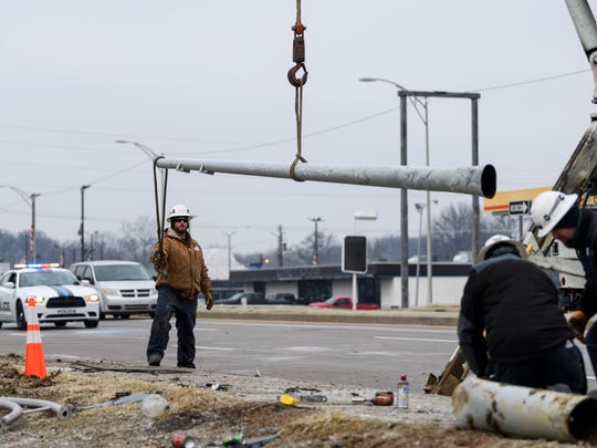 A crew of Vectren workers clean up a fallen light pole after a driver crashed into it and ran into parked cars in the S & A Auto Sales used car lot near the intersection of Diamond and Heidelbach Avenues in Evansville, Ind., Wednesday morning, Feb. 7, 2018. There were no reported injuries, but two lanes of traffic on Diamond Avenue was blocked off while the clean up took place.