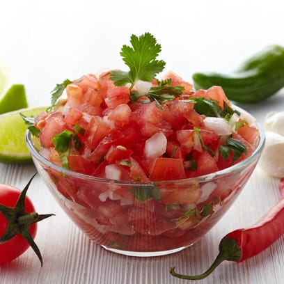 Bowl of fresh salsa dip and ingredients on white wooden background