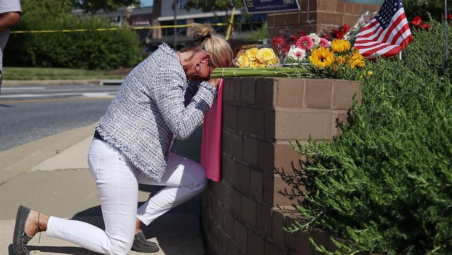 Lynne Griffin pays her respects at a makeshift memorial near the Capital Gazette where five people were shot and killed by a gunman on Thursday in Annapolis, Maryland.