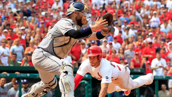 St. Louis Cardinals' Tommy Pham scores past San Diego Padres catcher Derek Norris in the eighth inning Saturday in St. Louis. The Cardinals won 2-1.