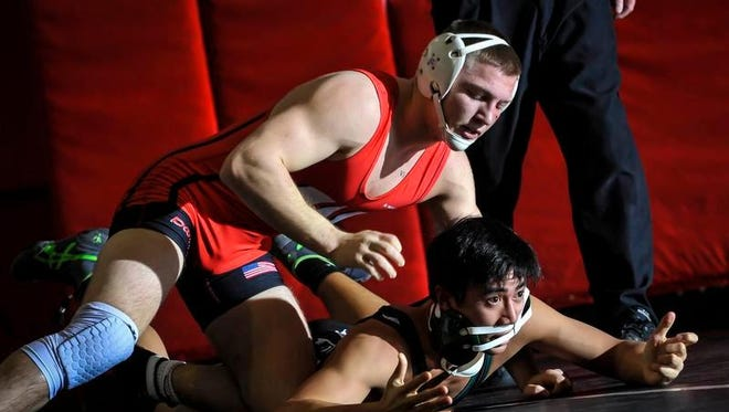 Woodbridge's Bryan McLaughlin (top) works to score points against Long Branch's Justin Navarro during their 195-pound match on Saturday at Woodbridge High School.