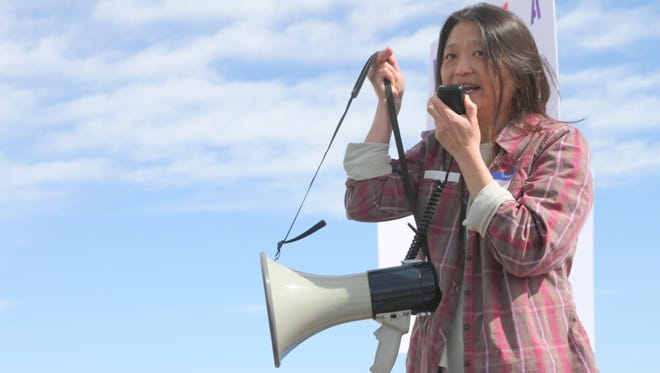 Naturalized American Josey Foo tells her story of once being an undocumented immigrant during a rally Saturday on the grounds at the Farmington Museum at Gateway Park