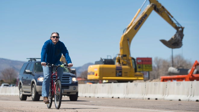 A cyclist passes construction as he travels eastbound on Mulberry Street on Wednesday, April 18, 2018.