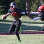 Wilson wide receiver Rickey Gamble, left, sheds tacklers as he races down the sidelines.