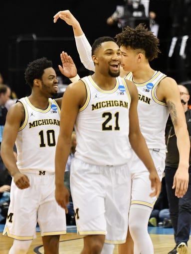 From left, Michigan teammates Derrick Walton Jr. (10),