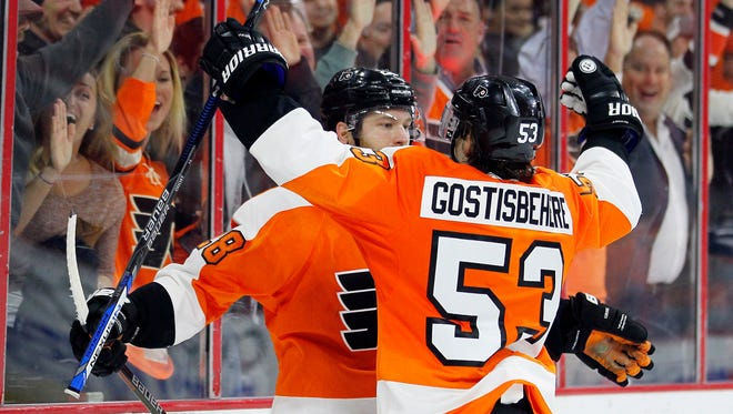 The Flyers' Shayne Gotisbehere, right, joins Claude Giroux, to celebrate after Giroux  scored the game-winning goal  during the overtime against the Winnipeg Jets on Monday.