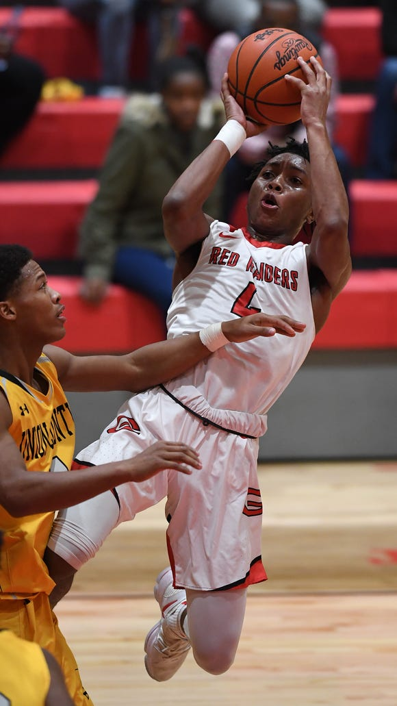 Greenville's Dorian Williams (4) shoots over Union County's KeSean Glover (4) during the Red Raiders' 65-60 win in the first round of the Class AAAA boys playoffs on Tuesday night at Greenville High.