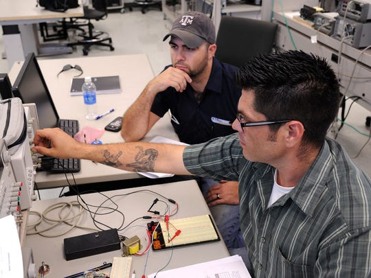 A Texas A&M-Corpus Christi Electrical engineering students measure the voltage of a circuit.
