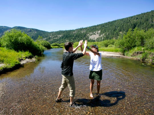 In this photo taken Tuesday, July 25, 2017, standing in the North Fork of Prosser Creek, Elliott Wright, left, of The Nature Conservancy and Kathy Englar, of the Truckee Donner Land Trust, celebrate the recent acquisition of property in the Lower Carpenter Valley near Truckee, Calif. Recently purchased by the Truckee Donner Land Trust, The Nature Conservancy and others, this meadow, hidden from public view for more than a century, is opening for tours.