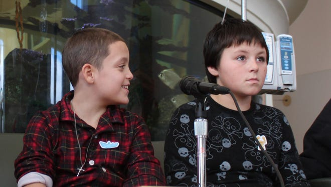Nine-year-old Jason Rivera, center left, and Elijah Martinez, 11, center right, are joined by their mothers, Aulix Martinez, left, and Deirdre Kirk during a news conference Friday at Westchester Medical Center's Maria Fareri Children's Hospital in Valhalla. The boys spent seven hours trapped in the snow the night before.