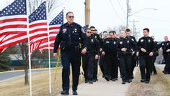 Law enforcement personnel walk along a line of flags