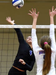 McQueen's Kaila Spevak goes up to spike the ball past Reno's Mia Wilmot in Tuesday's game at Reno.