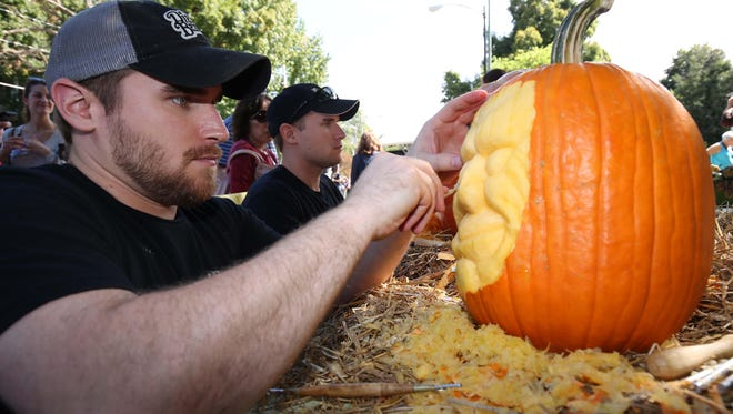 MB Creative Studio's Mike Brown, left, carves pumpkins with his brother Matt during Cider Days.