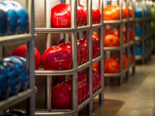 Bowling balls in racks are ready to go at Main Event