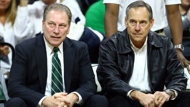 Michigan State basketball coach Tom Izzo, left, and football coach Mark Dantonio sit on the bench prior to a game against the Michigan Wolverines.