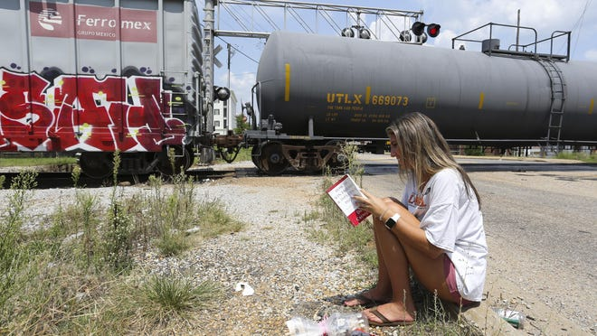 Blaine Bozeman sits on the side of the road and reads a book as she waits for a train to pass over the crossing at Hackberry Lane Monday, August 10, 2020. Bozeman is a University of Alabama student. Classes at UA are scheduled to begin Aug. 19.