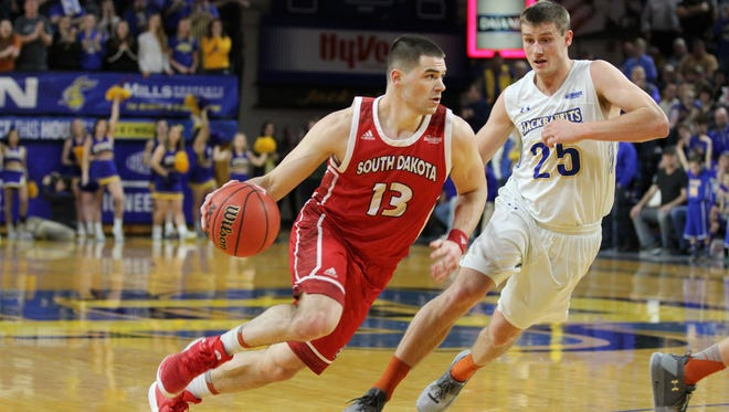 South Dakota's Matt Mooney (13) drives to the bucket past South Dakota Stae's Lane Severyn during the second half of the Jackrabbits' 76-72 victory over the Coyotes Thursday night at Frost Arena.