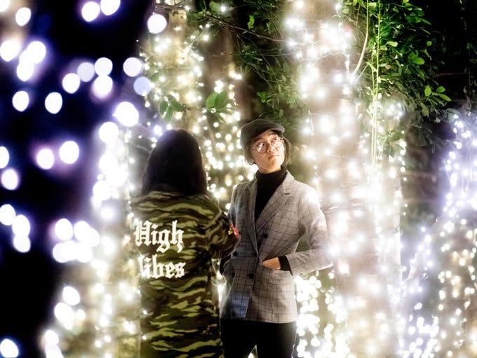 Michelle Kyu and Aye Kyi take photos among the lit