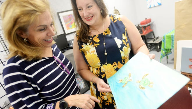 Artist Lynn Laird, right, shows her client Victoria Provenza the artwork she did for her.