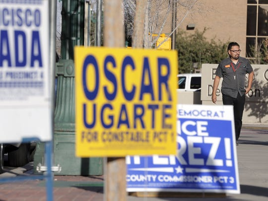 Pedestrians walk past campaign signs outside the polling station at the El Paso County Courthouse. Early voting runs through Feb. 26 for several primary races, including the presidential primary.