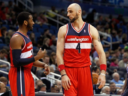Washington Wizards guard John Wall (2) and center Marcin Gortat (4) talk against the Orlando Magic during the second half at Amway Center on March 14, 2014.