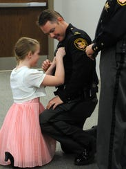 Jyllian Hodder, 11, pins a lieutenant's badge onto