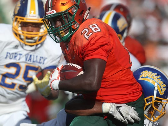 FAMU's Ricky Henrilus drags along defenders during a run against Fort Valley State University's as they open the season at Bragg Memorial Stadium on Saturday, Sept. 1, 2018.