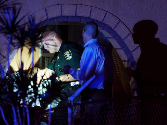 A Lee County Sheriff's deputy processes the scene of a shooting on the 2100 block of Davis Court in Fort Myers.