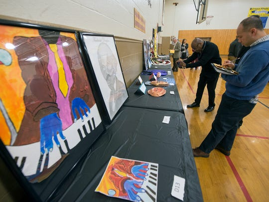 Tom Ho, with Lancaster Juvenile Probation, judges art work during the 22nd Annual African American History Fair on Tuesday. The event provides the opportunity for students to perform music and poetry, and to be judged onart and historical displays.