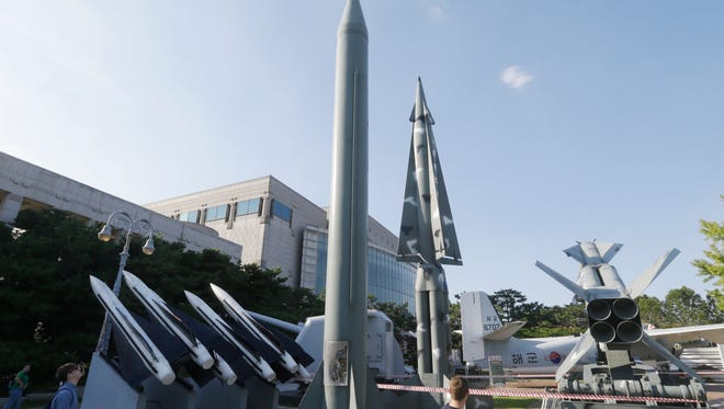 Visitors looks at models of North Korea's Scud-B missile, center left, and other South Korean missiles on display at the Korea War Memorial Museum in Seoul, South Korea, Tuesday, Sept. 15, 2015. A day after threatening long-range rocket launches, North Korea declared Tuesday that it has upgraded and restarted all its atomic fuel plants so it can produce more - and more sophisticated - nuclear weapons. (AP Photo/Ahn Young-joon)