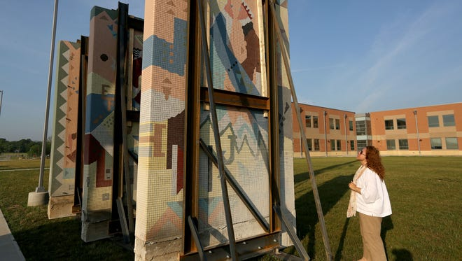 """Kelli Lobb Reisen, looks at murals removed from the old Princeton High School that now sits on the lawn at the new high school. Reisen is the project's organizer and a Princeton alumni. The mosaic depictions of Shakespeare's """"Seven Ages of Man"""" will be part of an amphitheater on the campus' northwest lawn."""