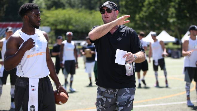 In this July 6, 2015, photo provided by Tom Hauck, former NFL player and current ESPN analyst Trent Dilfer, right, gestures while talking to Ohio State quarterback J.T. Barrett at the Elite 11 quarterback competition in Beaverton, Ore. Five years ago, Dilfer became the face and driving force behind Elite 11, a quarterback competition for top high school prospects that ESPN has turned into a reality show.