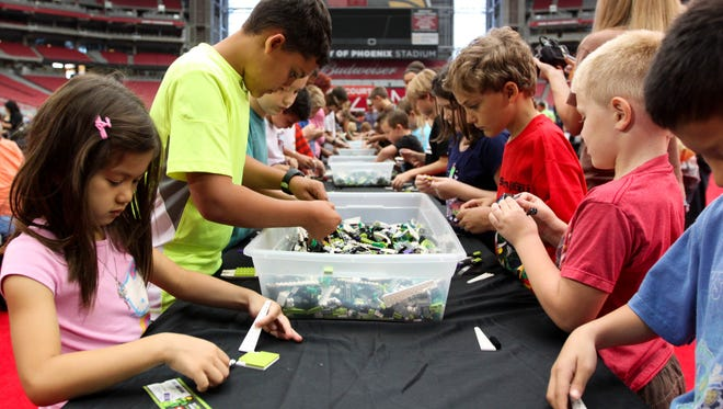 Kids try out their new skills during the Master Builder Academy at LEGO KidsFest at the University of Phoenix Stadium in Glendale.