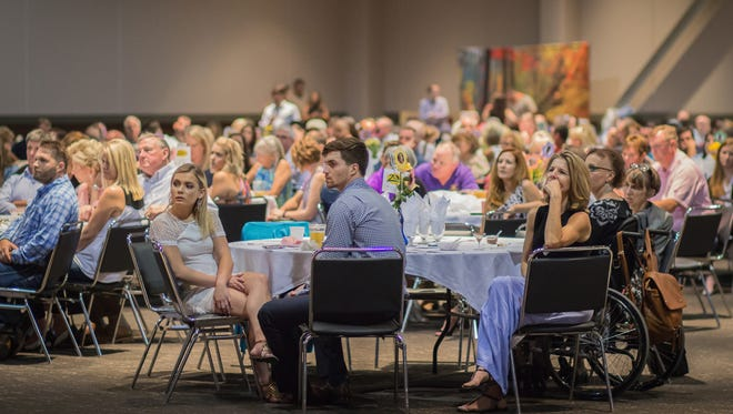 Attendees watch the final presentations at the 100 Men Who Cook fundraiser. The Ark Crisis Center received $221,000 from the Aug. 27 event at Old National Events Plaza.