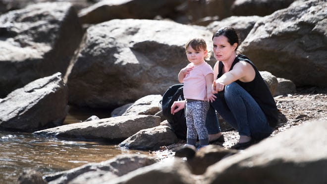 Crystal Mills points out a duck to her daughter, Ruby, 1, while taking a break from working in Falls Park on Wednesday, January 18, 2017.