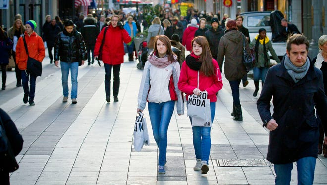 Pedestrians and shoppers pass stores on Drottninggatan, a main shopping street, in Stockholm, Sweden.
