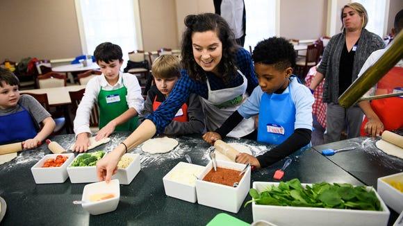 Hannah Schmunk helps fourth graders from the Boy &